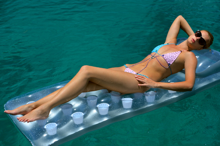 Woman in bikini sunbathing on floating device at open waters of carribbean photo