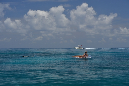 Woman in red bikini on floating device at open waters of carribbean with scuba boat photo