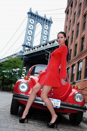 Young brunette posing in red dress in front of vintage car with view to Manhattan bridge at Dumbo area in Brooklyn NY