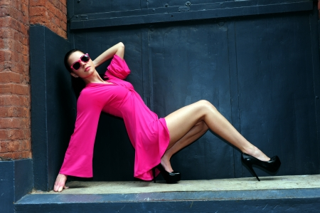 Young brunette posing in pink dress and sunglasses in front of metal door at Dumbo area in Brooklyn NY photo