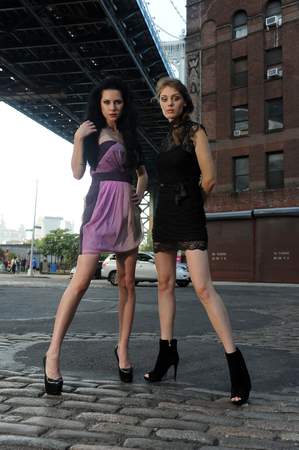 Two models posing standing under Manhattan bridge at Dumbo area in Brooklyn NY photo