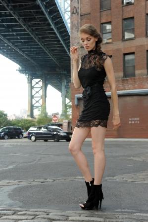 Jonge vrouw draagt zwarte minijurk staande onder Manhattan Bridge bij Dumbo gebied in Brooklyn NY