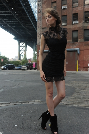 Young woman wearing black minidress standing under Manhattan Bridge at Dumbo area in Brooklyn NY