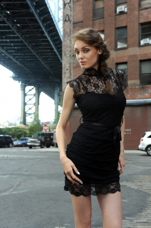 Young woman wearing black minidress standing under Manhattan Bridge at Dumbo area in Brooklyn NY photo