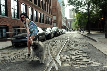 ブルックリンのダンボ地区に歴史的古い路面レールで若いブルネット持株犬 写真素材