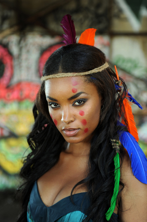 Portrait of young beautiful indian cherokee woman with feathers in her hair and traditional makeup on abstract background