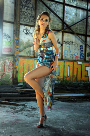 abandoned warehouse: Young model wearing designers dress at grunge background of abandon werehouse