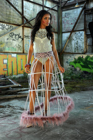 Attractive african american woman wearing swimgerie top and cage skirt at abandoned wearhouse background photo