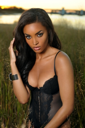 Beautiful african-american woman wearing black lingerie corset at the sunset at grass field
