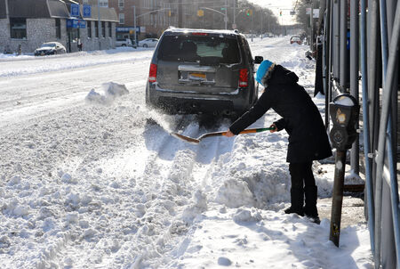 People cleaning streets in Brooklyn after the seasons first snow storm in New York City