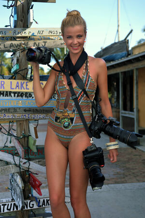 Model holding three professional photo cameras at tropical location of Key West, FL with old signpost at background