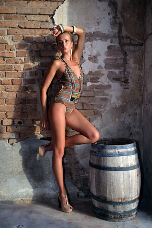 Seductive swimsuit model posing sexy in front of old fort brick walls in Florida