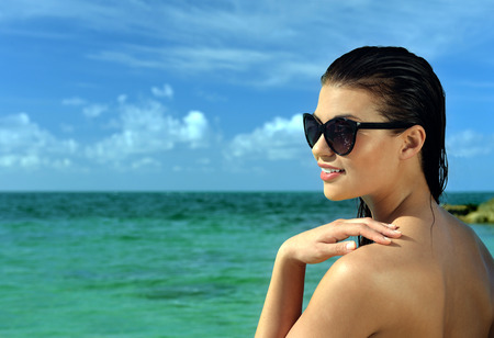 Woman wearing swimsuit and sunglasses standing inshallow tropical water