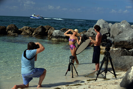 Photographers assistant helping photographer to control light over swimsuit model at location shoot at tropical beach