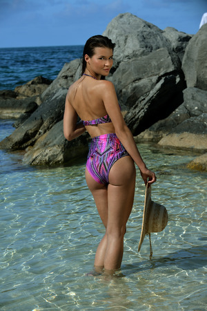 Model posing at tropical location showing back of her swimsuit