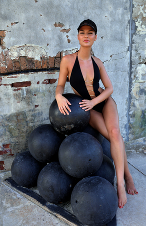 Swimsuit model sitting on cannon balls at fort Zahariy in Key West, FL
