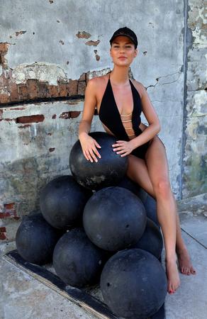bombard: Swimsuit model sitting on cannon balls at fort Zahariy in Key West, FL