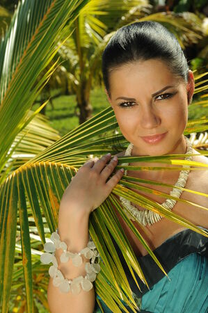 american sexy: Attractive brunette in fashion dress standing in front of palm tree