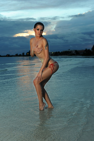 Topless girl in red bikini bottom posing sexy at shallow tropical water after sunset photo