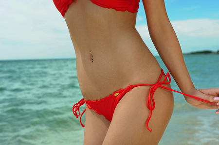 Sexy slim bikini model wearing red bikini at tropical location photo