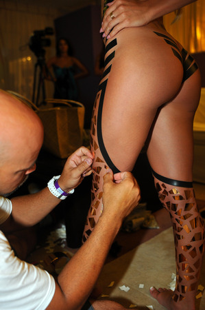 btp: CANCUN, MEXICO - MAY 04: Artist applying electrical tape to model at his Black Tape Project during IBMS 2014 on May 04, 2014 in Cancun, Mexico. Editorial