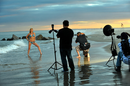 photo shooting: Photographers and bikini model in summer photoshooting on the beach during sunset time. Stock Photo