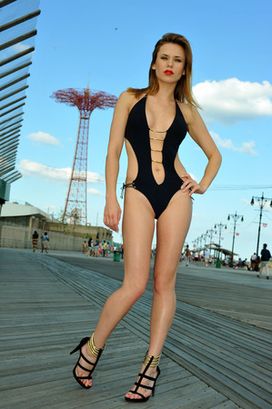 Sexy swimsuit model posing on the boardwalk with parachute jump on the background. Coney Island, Brooklyn, New York.