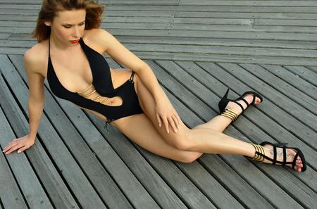Fashion model posing on boardwalk wearing black swimsuit and high heels sandals.