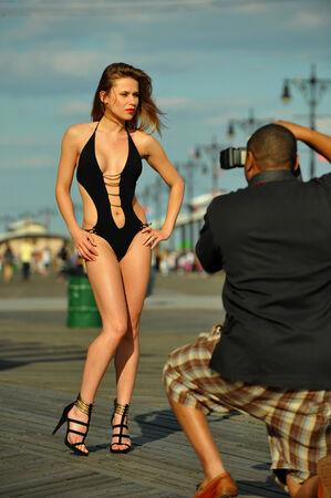Fotógrafo con la cámara que toma imágenes de la bella joven modelo del traje de baño en el paseo marítimo en tiempo de verano. Foto de archivo