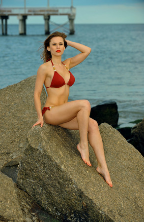 Beautiful fashionable woman in red bikini sitting on the rocks at the beach.