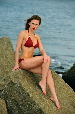 Young sexy woman in red bikini at the beach.Sensual attractive woman in swimsuit. Caucasian woman with perfect body relaxing on the rock.