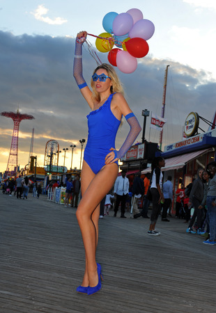Fashion beautiful young woman holding baloons wearing blue swimsuit and gloves posing outdoors with amusement park on background.