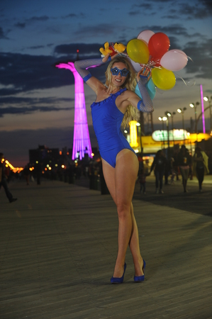 Fashion beautiful young woman holding baloons wearing blue swimsuit and gloves posing outdoors with amusement park on background. photo