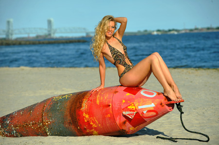 Young beautiful fashion model in onepiece swimsuit and posing at the beach sitting on the bouy.