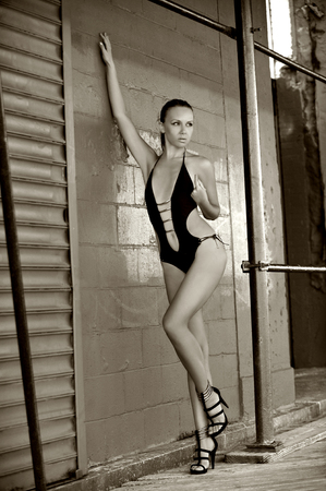 Brunette swimsuit model posing sexy outdoor in front of metal gate.Black and white picture. photo