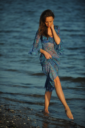 transparent dress: Alluring sexy woman posing on the beach in floral transparent dress. Beautiful happy brunette girl enjoying hot summer sun. Romantic slim lady at vacation walking on the ocean shore.
