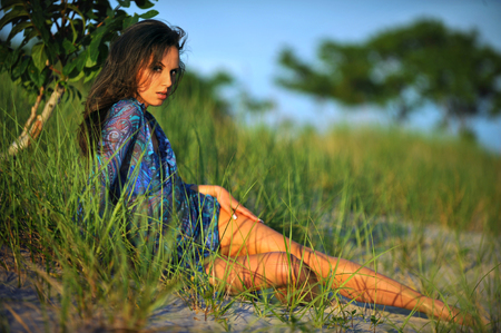 transparent dress: Beautiful young woman in floral transparent dress posing pretty on the beach.Beautiful happy brunette girl enjoying hot summer sun. Romantic lady at vacation. Stock Photo