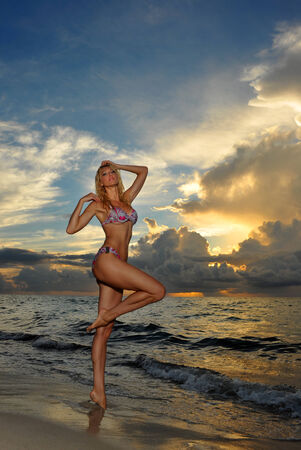 Model posing in bikini at early morning sunrise over the ocean at tropical location photo
