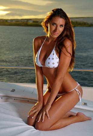 bikini model: Attractive swimsuit model wearing white stylish bikini posing on deck of motor boat in sunset light.