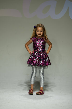 eveningwear: NEW YORK, NY - OCTOBER 19: A model walks the runway during the Clarks preview at petitePARADE Kids Fashion Week at Bathhouse Studios on October 19, 2014 in New York City.