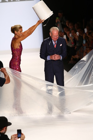 als: NEW YORK, NY - SEPTEMBER 05: Heidi Klum pours ice on Tim Gunn for the ALS Ice Bucket Challenge during the Project Runway Season 13 Finale Show during MBFW Spring 2015 on September 5, 2014 in NYC
