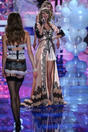 november 3d: LONDON, ENGLAND - DECEMBER 02:  Singer Taylor Swift (L) perfoms on stage as model Sigrid Agren (R) model walks the runway during the 2014 VS Fashion Show on December 2, 2014 in London, England.