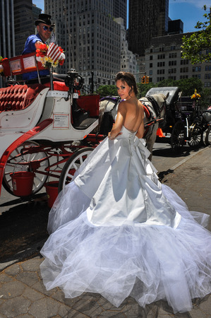 horse and carriage: NEW YORK - June 13: Model Kalyn Hemphill pose in front of horse carriage at the Irina Shabayeva SS 2016 Bridal collection photoshoot on June 13, 2015 in New York, USA