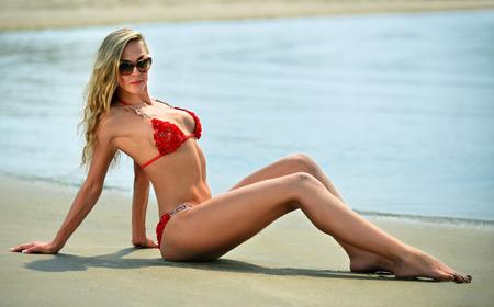 blonde bikini: Young beautiful sexy blonde bikini model, laying on the ocean beach.