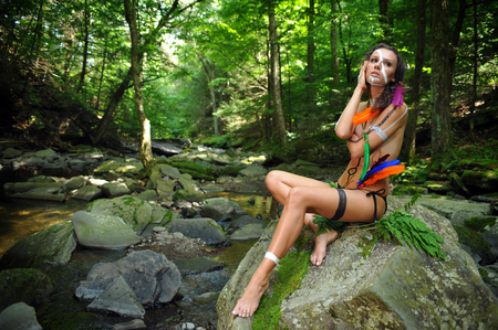 sexy nude women: Artistic shoot of glamour model wearing bikini bottom, feathers and native american  style face and body paint at the wild forest and mountains location.