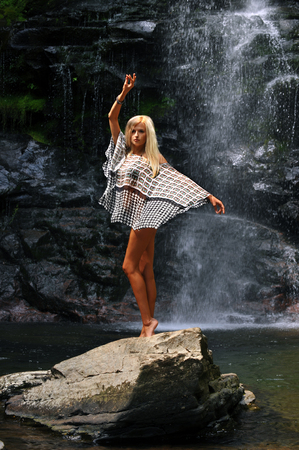 waterfall model: Beautiful young fashion model posing at the wild nature location. Waterfall background.