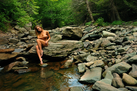 nude nature: Artistic photo of nude elegant young woman posing at mountain river with green wild forest on the background. Stock Photo