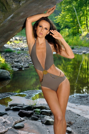 waterfall model: Sexy young woman with slim perfect figure posing in design swimsuit at exotic location of mountain river with rocks and forest on the background. Stock Photo