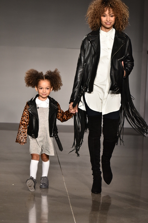NEW YORK, NY - OCTOBER 17: Mother and kid model walks runway at Laer Fall/Winter 2016 Runway Show during petiteParade at The Spring Studio on October 17, 2015 in NYC. Editoriali