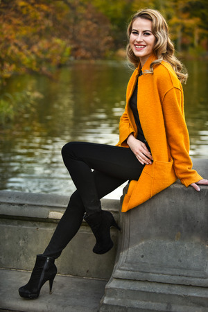 Smiling young model posing in a park in autumn.